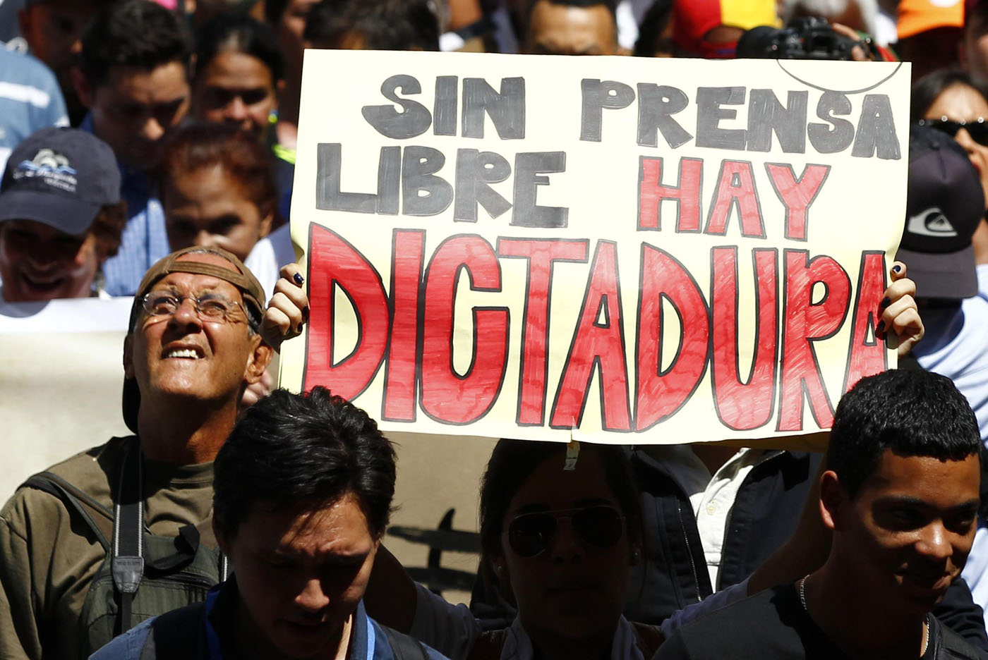 "A woman holds up a sign reading ""'Without free press, there is a dictatorship"", during a protest by newspaper workers and opposition parties to demand from the government U.S. dollars at a prime rate to buy paper for their publications, in Caracas February 11, 2014. Newspaper owners claim they are close to running out of their stock of paper due to the lack of dollars to import it, local media said.  REUTERS/Carlos Garcia Rawlins (VENEZUELA - Tags: POLITICS CIVIL UNREST MEDIA BUSINESS)"